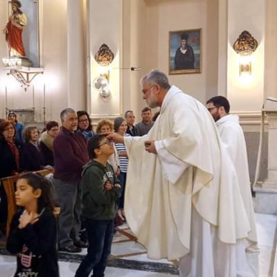 Un padre gesuita e un bambino durante una celebrazione presso la Chiesa del SS. Crocifisso dei Miracoli a Catania