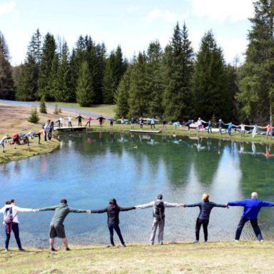 Giovani ignaziani in cerchio intorno a un laghetto per celebrare la cura del creato
